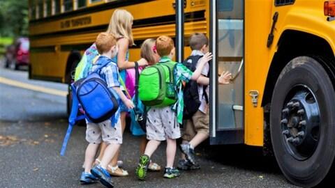Des enfants avec des sacs à dos montent dans un bus