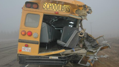L'épave d'un autobus scolaire accidenté, au bord d'une route.