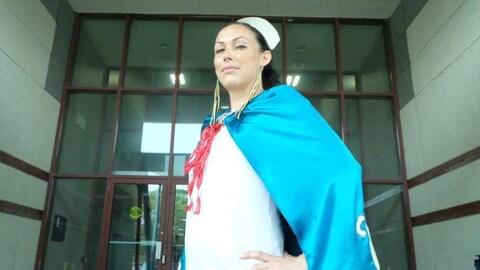 Lela George habillée en Nurse Hope prend une pose héroïque devant le centre communautaire de sa communauté.