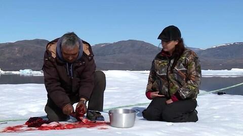 Un homme et une femme inuits préparent de la viande à l'extérieur.