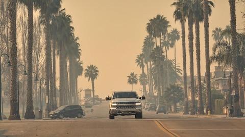Automobiles dans une rue sous un ciel enfumé