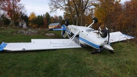 Un petit avion blanc et bleu à l'envers sur du gazon