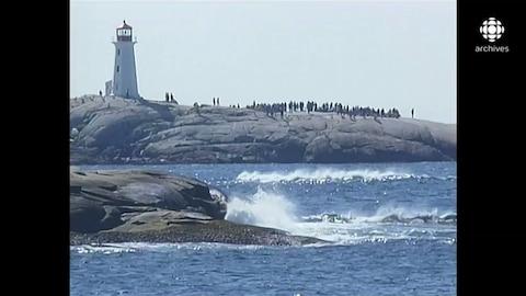 Des familles des victimes se recueillent sur les rochers à côté du phare de Peggy's Cove.