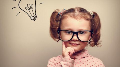 Une fillette avec des lunettes et une ampoule dessinée au-dessus de la tête.