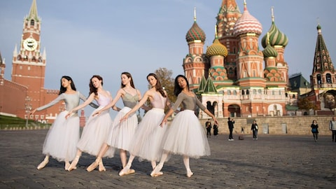 Des danseuses du Ballet national du Canada prennent des poses de danse alors qu'on voit derrière elle des édifices de la Place-Rouge.