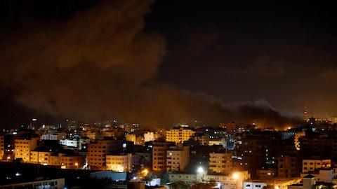 De la fumée est visible au-dessus de bâtiments dans la bande de Gaza.
