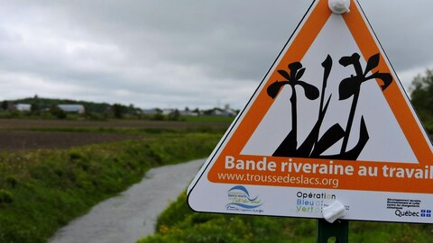 On voit en gros plan le panneau sur lequel est écrit « Bande riveraine au travail ». En arrière-plan, le cours d'eau, un champ et des bâtiments agricoles.