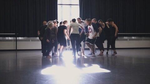 Un groupe d'acteurs, debout, en cercle comme une meute, au centre d'un plateau éclairé par le soleil.