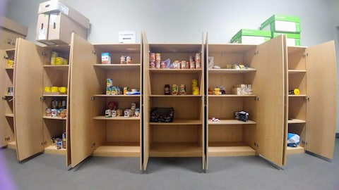 Des dizaines de conserves de soupe et autres aliments sont alignées dans des armoires, tandis que quelques étagères sont complètement vides.