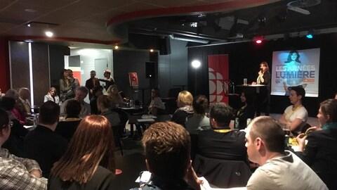 Des gens dans un bar écoutant l'animatrice Sophie-Andrée Blondin.