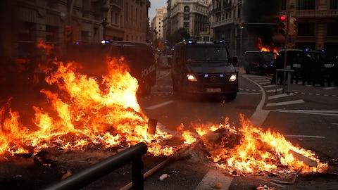 Des objets en feu au milieu d'une rue barrent le chemin aux camions de la police de Barcelone.