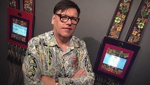 Un artiste pose devant deux de ses oeuvres.