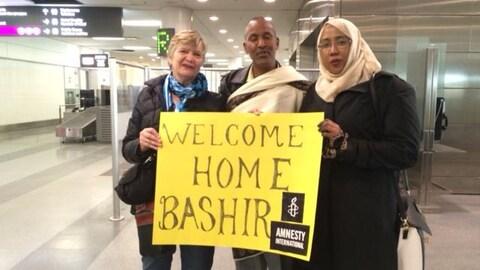 """Bashir Makhtal à son arrivée à l'aéroport Pearson de Toronto pose entre deux femmes et derrière une pancarte sur laquelle est écrit """"Welcome Home Bashir"""" et Amnesty international"""