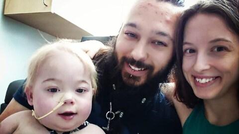 Des parents posent avec leur bébé intubé dans un hôpital.
