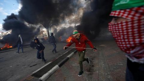 Des Palestiniens courent dans les rues de Beit El, où des incendies ont été allumés.