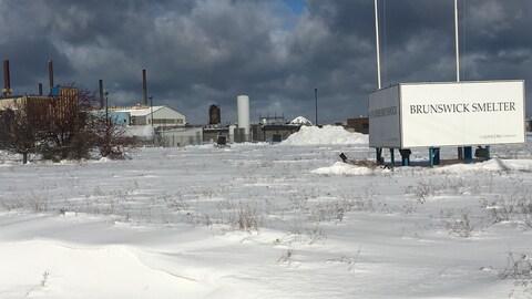 Un terrain enneigé au fond duquel on peut apercevoir une grande usine.