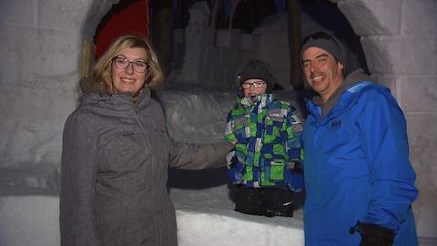 Deux parents et leur enfant devant une structure en neige.