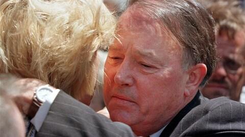 Bernard Landry, le visage attristé, serre quelqu'un dans ses bras.