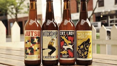 Quatre bouteilles de différentes bières vendues par la brasserie Bellwoods sont alignées sur une table en bois, dans une rue.