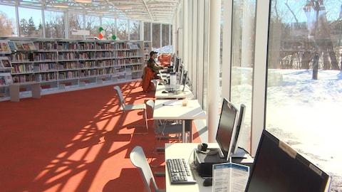 Dans une bibliothèque, une rangée d'ordinateurs devant des fenêtres ensoleillées qui donnent sur un petit parc enneigé.