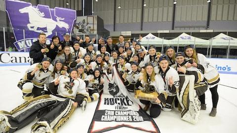 Une photo d'équipe en équipement sur la glace avec le trophée et des médailles.