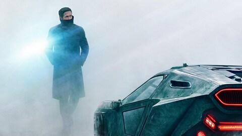 L'affiche du film « Blade Runner 2049 », réalisé par Denis Villeneuve: on y voit Ryan Gosling marcher à travers le brouillard vers sa voiture futuriste.