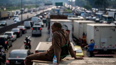 Un homme bloque partiellement la route et se repose sur son camion, avec une bouteille d'eau.