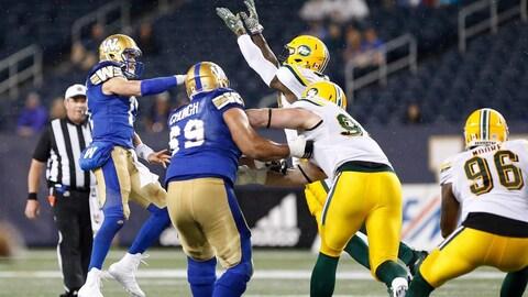 Des joueurs de football des Blue Bombers de Winnipeg et des Eskimos d'Edmonton se disputent le ballon.