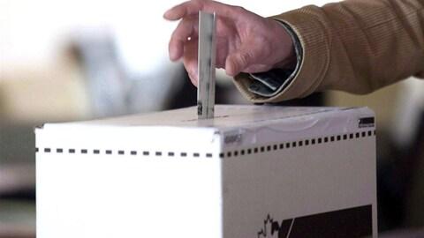 Un bulletin de vote est déposé dans une boîte de scrutin