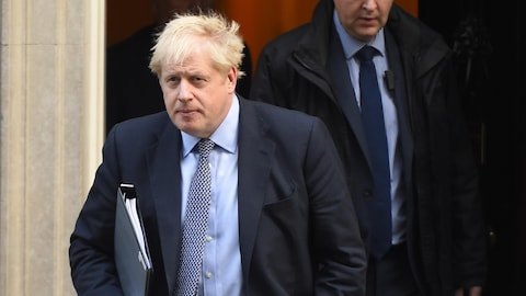 Boris Johnson marche, un cartable sous le bras.