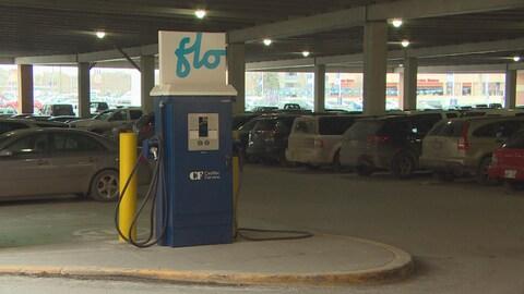 Une borne de recharge bleue et blanche portant les lettres flo se trouve au rez-de-chaussée d'un stationnement à étage.