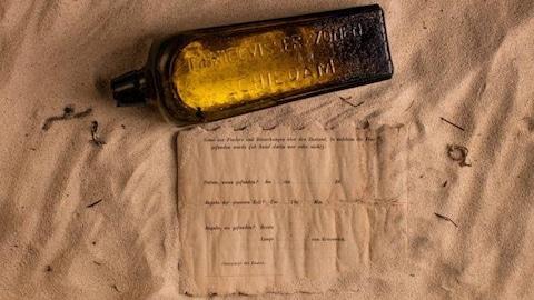 Une bouteille brune et une lettre étendues sur du sable.