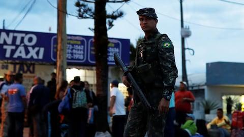 Des soldats de l'armée patrouillent dans une rue à côté des Vénézuéliens après avoir vérifié leur passeport ou leur carte d'identité à la frontière de Pacaraima.
