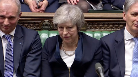 Theresa May, l'air défait, est assise au Parlement.