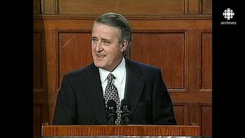 Brian Mulroney, souriant, derrière un lutrin