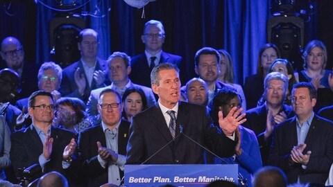 Brian Pallister le soir de son élection en avril 2016. Il parle devant un micro. Une foule qui applaudit se trouve derrière lui.