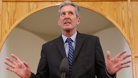 Brian Pallister, en costume cravate, lève les mains devant un micro, l'air surpris.