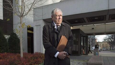 Bruce Carson se tient debout à l'extérieur de la Cour, un dossier dans les mains.