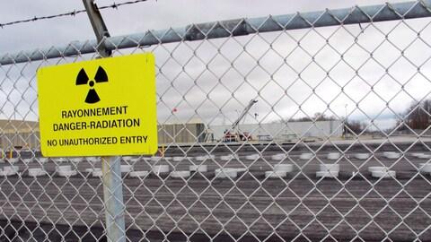 En avant-plan, une clôture avec une affiche où il est écrit : « Rayonnement Danger-Radioation, entrée non autorisée interdite ». En arrière-plan, une zone industrielle.