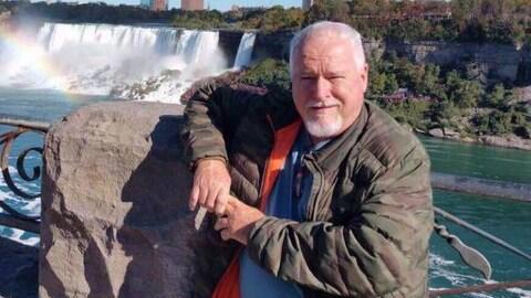 Le portrait d'un homme devant une chute d'eau