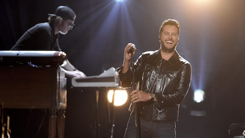 Luke Bryan est debout sur scène devant ses musiciens