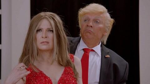 Une femme en robe du soir et un homme en costard posent côte à côte.