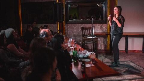 Dans une salle, une femme se tient debout avec un mciro en mains, devant un public de gens qui sont assis à des tables.