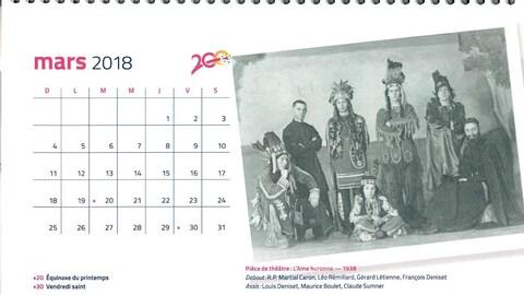 La page de mars du calendrier de 2018 de l'Université de Saint-Boniface. Il y a une photo de cinq jeunes déguisés en autochtones, accompagnés d'un prêtre en habits.