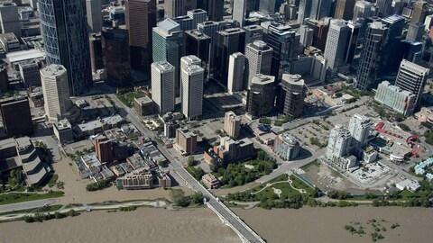 Vue aérienne du centre-ville de Calgary près d'une rivière qui déborde dans les rues voisines.