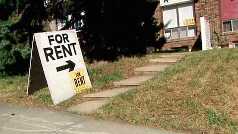 Vue sur le terrain devant une maison où il y a un panneau sur lequel il est écrit: À louer.