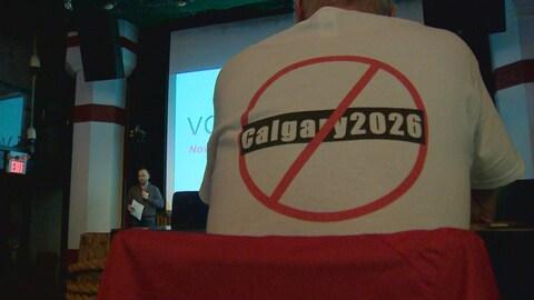 Un homme porte un chandail avec Calgary 2026 marqué d'un signe d'interdit pour signifier son opposition à ce que Calgary soumette sa candidature.