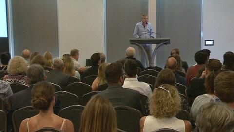 Vue sur une salle remplie de personnes qui écoutent un homme debout sur un podium.