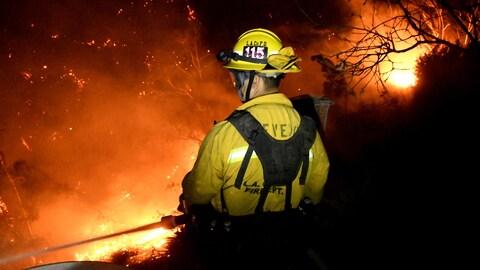 Un pompier arrose un brasier dans la nuit.