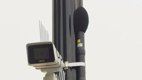 Une caméra blanche et un microphone sont accrochés à un poteau noir.